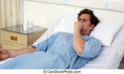 Sick man lying on hospital bed coughing - Sick man lying on...