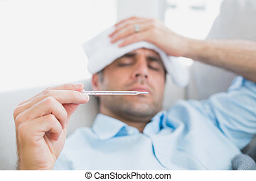 Sick man lying on sofa checking his temperature at home in...
