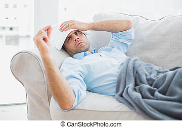 Sick man lying on sofa checking his temperature under a blanket