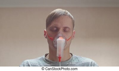 Sick man napping in oxygen mask portrait closeup unshaven messy male interior look into the camera