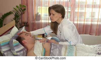 Sick man on bed - woman nursing him