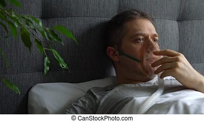 Sick man with inhalator mask on the face in bed. Coronavirus...
