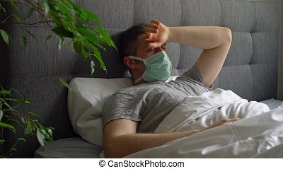 Sick man with medical mask lying in bed.