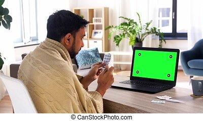sick man with medicine having video call on laptop - ...