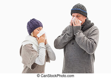 Sick mature couple blowing their noses on white background