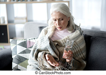 Sick mature lady curing herself by medication