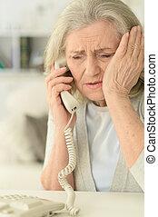 Sick mature woman calling doctor