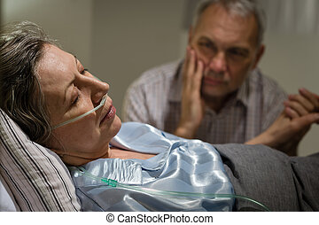Sick mature woman lying in bed worried husband holding hands