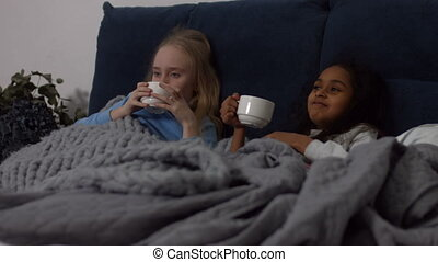 Sick multi ethnic kids drinking hot tea in the bed