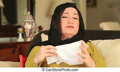 Sick muslim woman sneezing