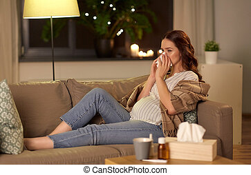 sick pregnant woman blowing nose at home