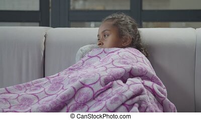 Sick sad african girl wrapped in blanket at home