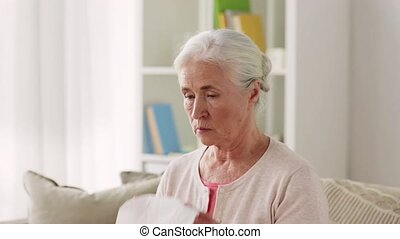 sick senior woman blowing nose to paper napkin - health,...