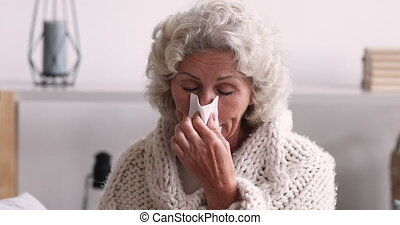 Sick senior woman covered with blanket blowing runny nose