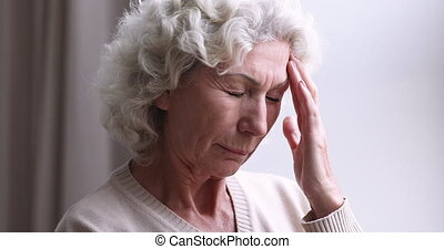 Sick senior woman having headache concept. Tired older 70s grandmother feeling pain or strong migraine touching aching head. Elder lady hypertension sufferer having memory loss problem. Close up view