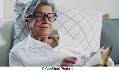 Sick senior woman lying in bed at home or in hospital,...