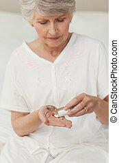 Sick senior woman taking her pills
