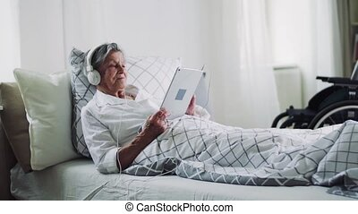 Sick senior woman with headphones and tablet lying in bed at...
