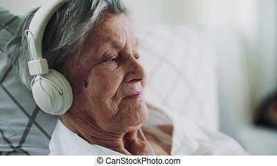 Sick senior woman with headphones lying in bed at home or in hospital. Slow motion.