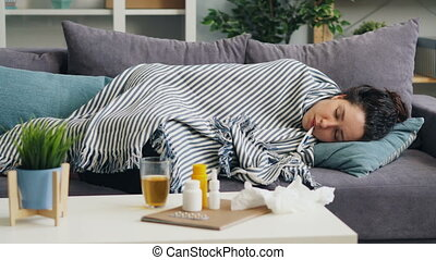 Sick student napping with thermometer in mouth lying on...