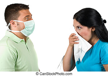 Sick woman having flu and sneeze in a white napkin and the man are terrified, wearing a protective mask and making big eyes when she sneezing isolated on white background