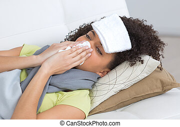 sick woman blowing her nose on sofa at home