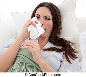 Sick woman blowing lying on a bed at home