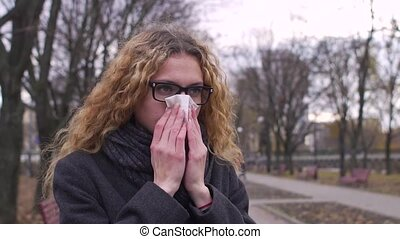 Sick woman blowing nose in cold weather, slow motion.