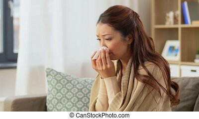sick woman blowing nose in paper tissue at home - healthcare...