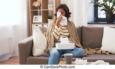 sick woman blowing nose in paper tissue at home -...
