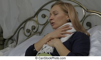 sick woman coughing and drinks a pills. girl lies in a bed with a warm scarf around his neck. slow motion