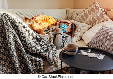 Sick woman having flu or cold. Girl lying in bed with cat wearing protective mask by pills and water on table