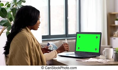 medicine, healthcare and technology concept - sick young woman having video call or online consultation on laptop computer with chroma key green screen at home talking about her symptoms and coughing