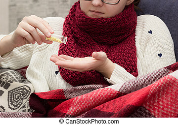 Sick woman in a scarf takes pills