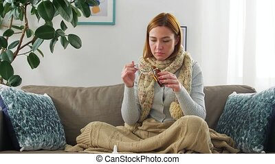 people, health and cold concept - sad sick woman in blanket and scarf drinking cough syrup at home