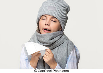 Sick woman in winter scarf and hat holding handkerchief sneezing
