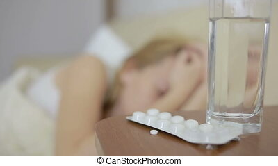 sick woman lying on the bed. pills and glass of water. drink tablets. painkiller