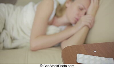 sick woman lying on the bed. pills and glass of water. drink...