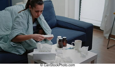 Sick woman shivering and reading package leaflet of medicaments for treatment instructions. Person feeling cold in blanket and looking at medicine paper to cure virus infection.