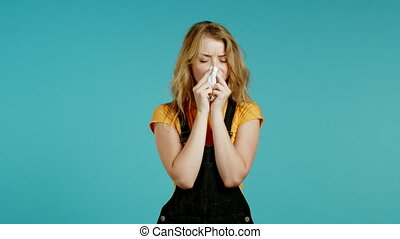 Sick woman sneezes into tissue. Isolated on blue studio background. Girl is ill, has a cold or allergic reaction. Coronavirus, epidemic 2020, illness concept.