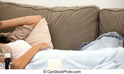 Sick woman sneezing lying on sofa at home