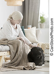 Sick woman stroking dog assistant