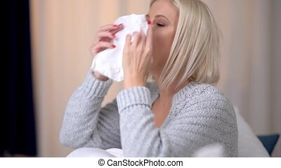 Sick woman suffering in bed with the flu virus blows her nose on a tissue.