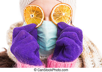 Sick woman wearing surgical mask and orange slices