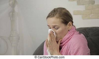 sick woman wipes his nose using a napkin and sneezes loudly.