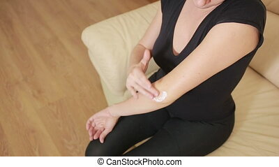 sick woman with an elbow. joint pain. pain cream. Girl rubs...