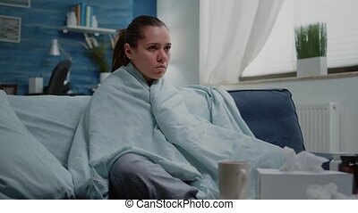 Sick woman with seasonal flu shivering in blanket at home. Cold adult sitting in living room with medicaments, treatment and cup of tea to cure virus infection and disease. Ill person