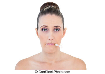 Sick woman with thermometer on mouth looking at camera...