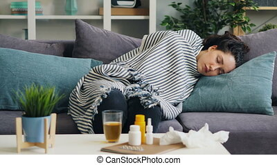 Sick young lady napping on couch at home under warm blanket...