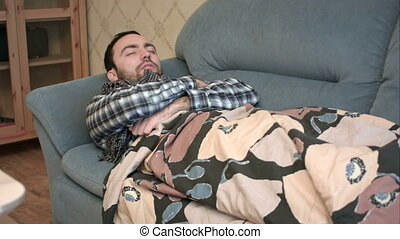 Sick young man in scarf sleeping in bed